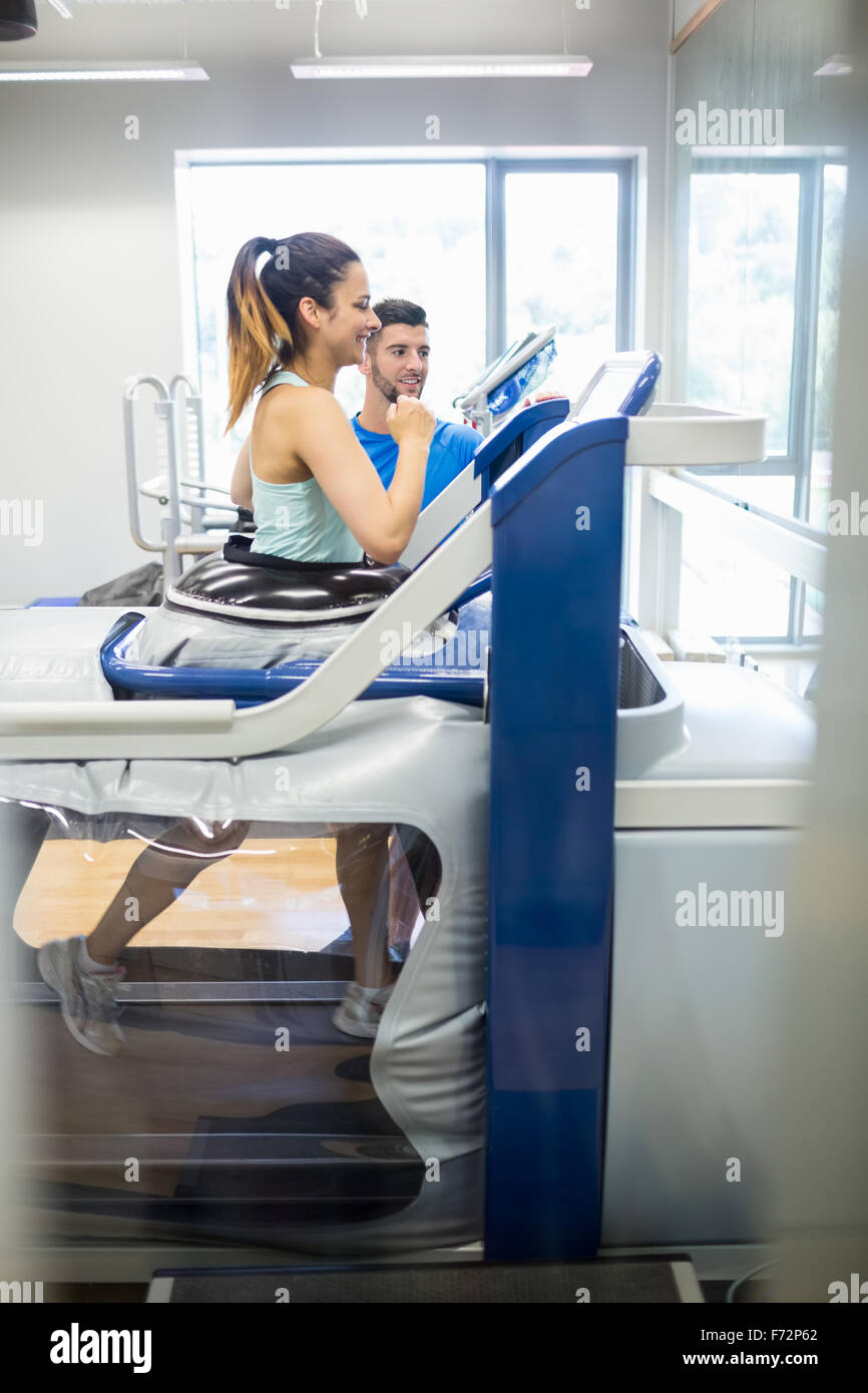 Woman using an anti gravity treadmill beside trainer - Stock Image
