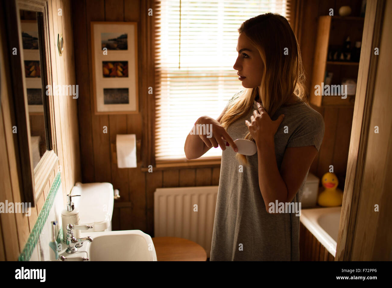 Pretty woman brushing her hair in the bathroom - Stock Image