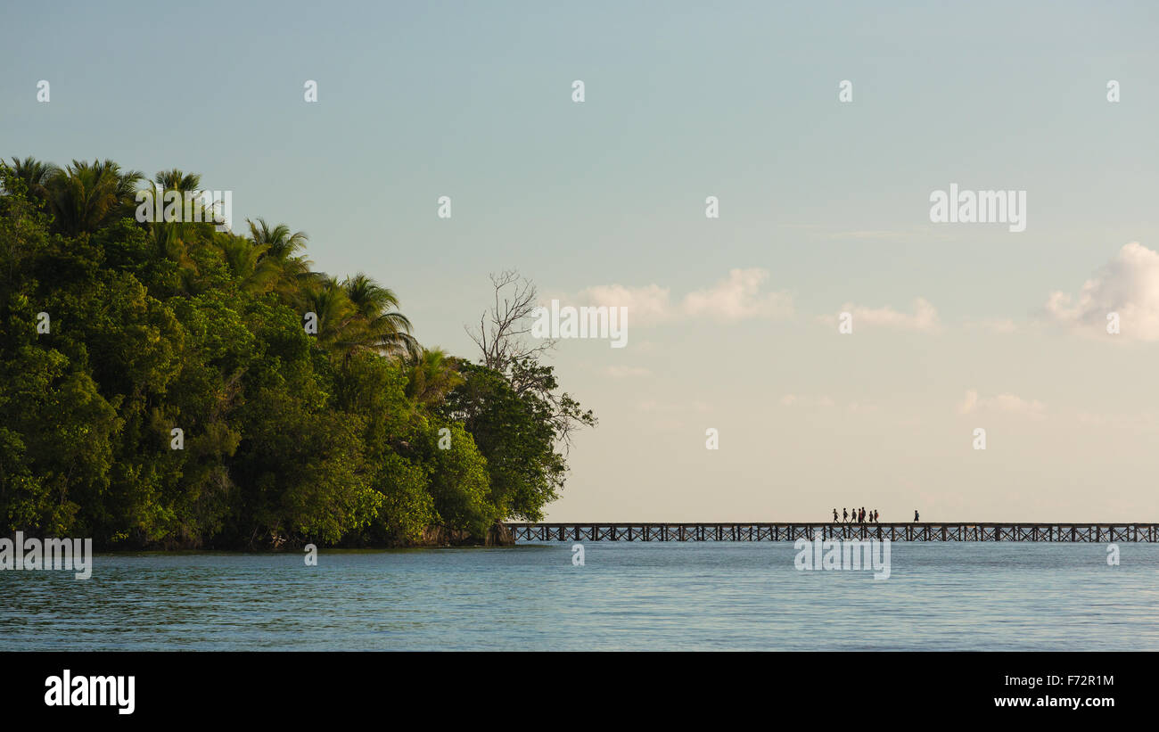 Panorama of the indigenousness people from the Bajo village on the Togean Islands crossing the bridge to the mainland, - Stock Image