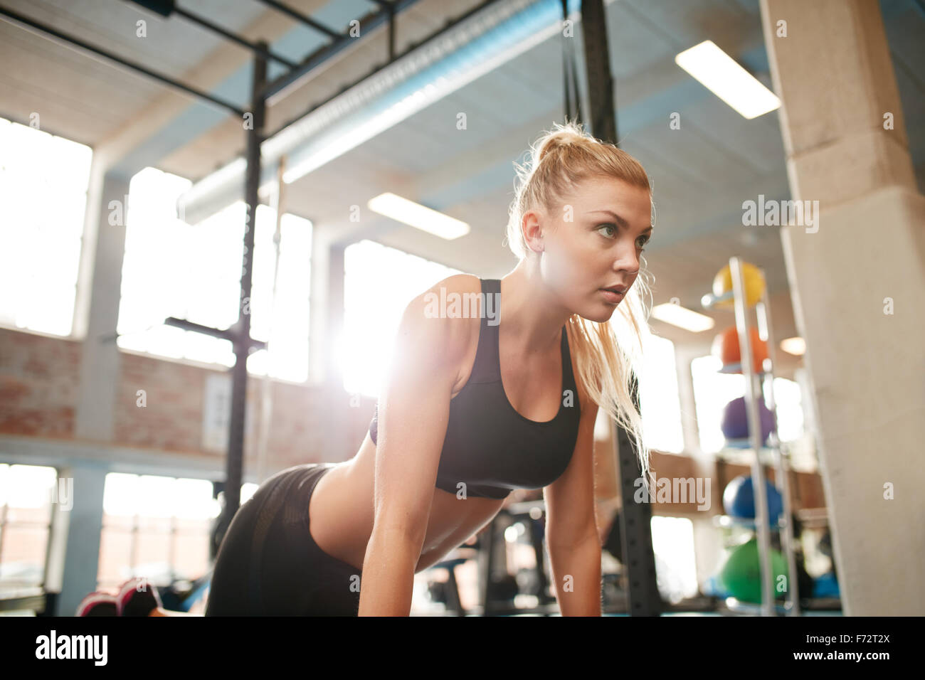 Indoor shot of young fitness woman doing push ups in gym. Caucasian female working out in health club. - Stock Image