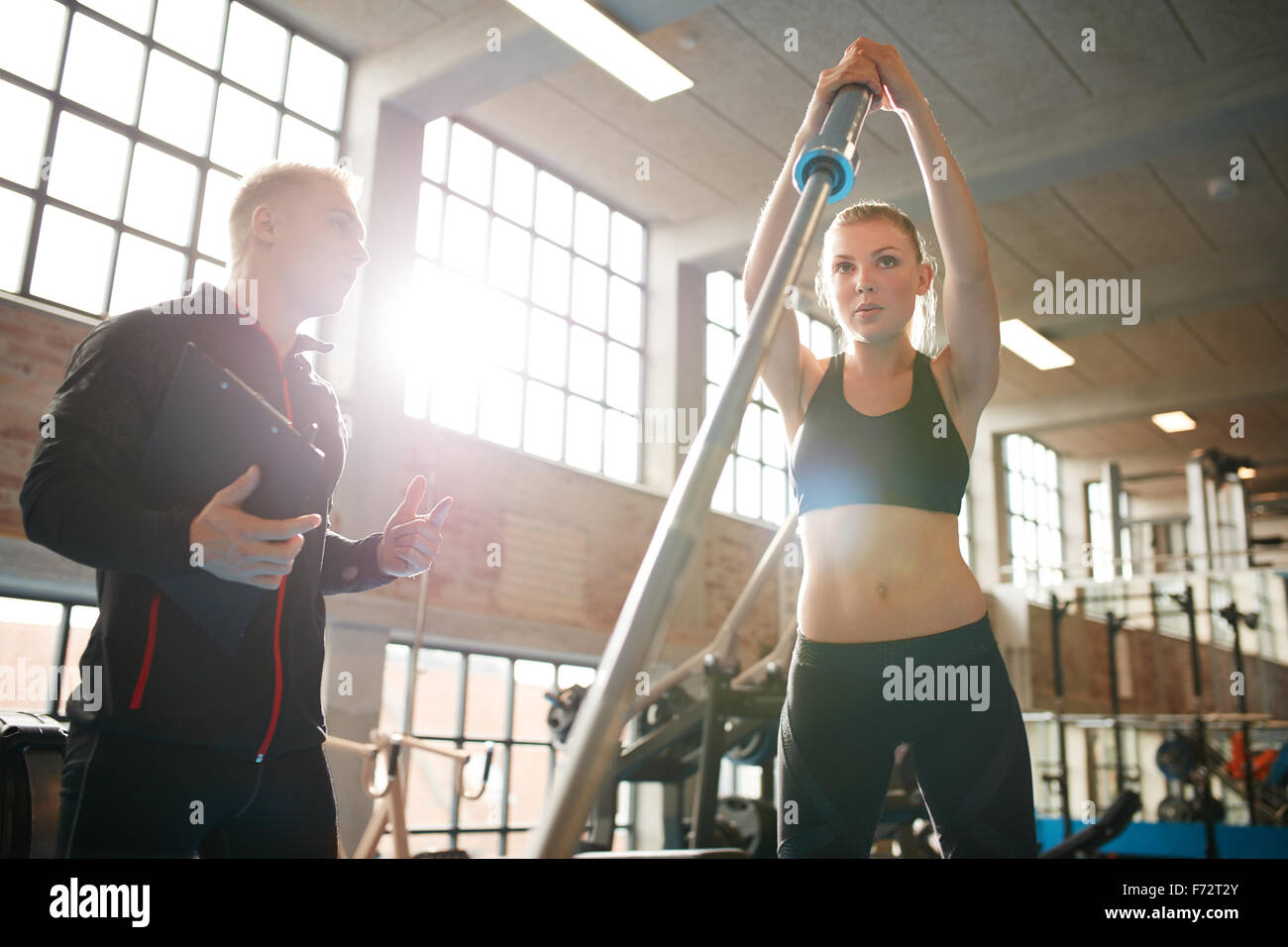 Portrait of young woman exercising with trainer at fitness center. Female working out with barbell being instructed - Stock Image