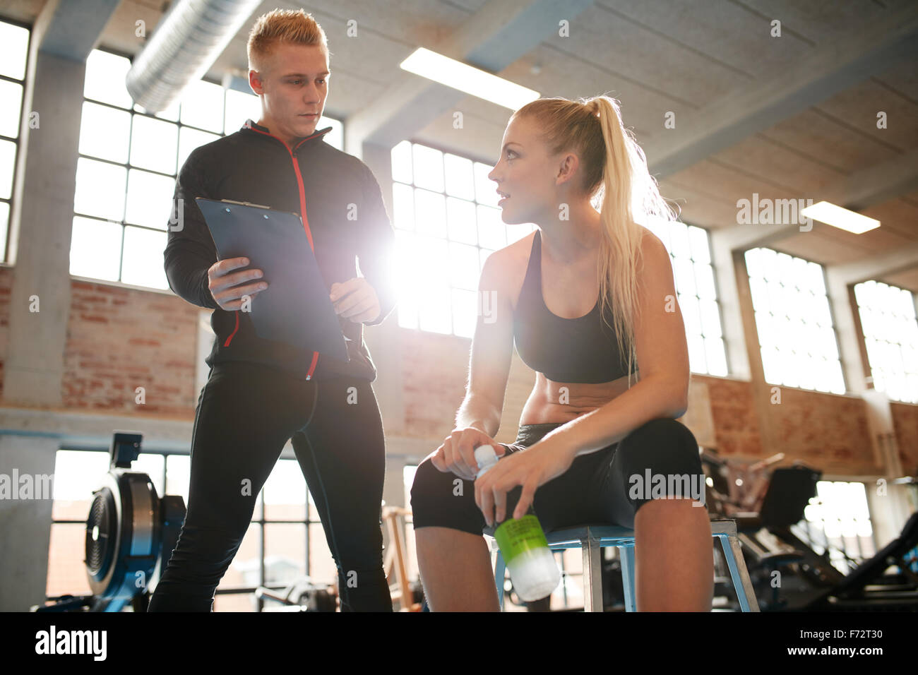 Young woman sitting on a stool and discussing exercise plan with personal trainer. Trainer making an fitness plan - Stock Image