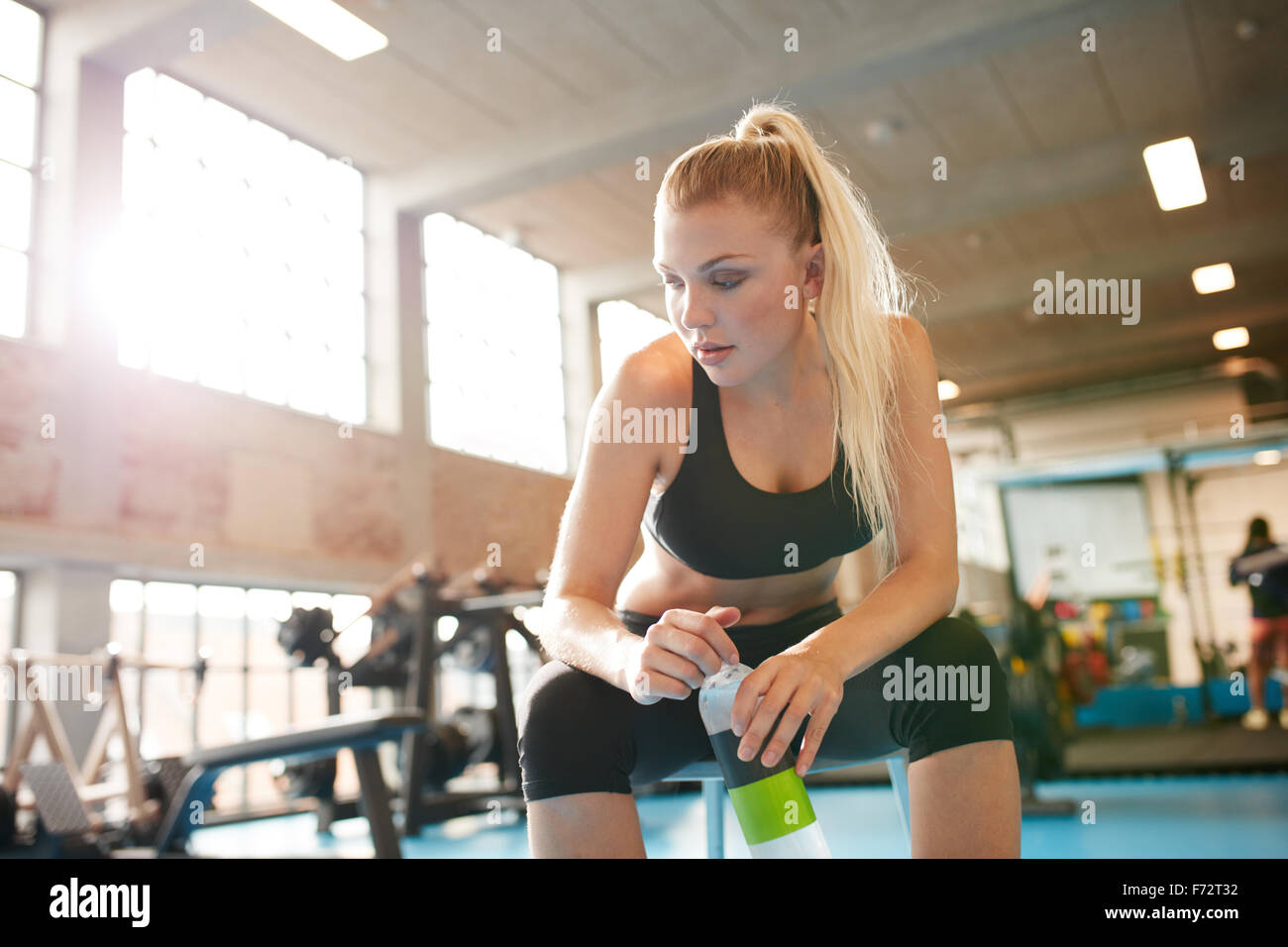 Portrait of young woman resting after workout at gym. Fitness female taking break after training session in health - Stock Image