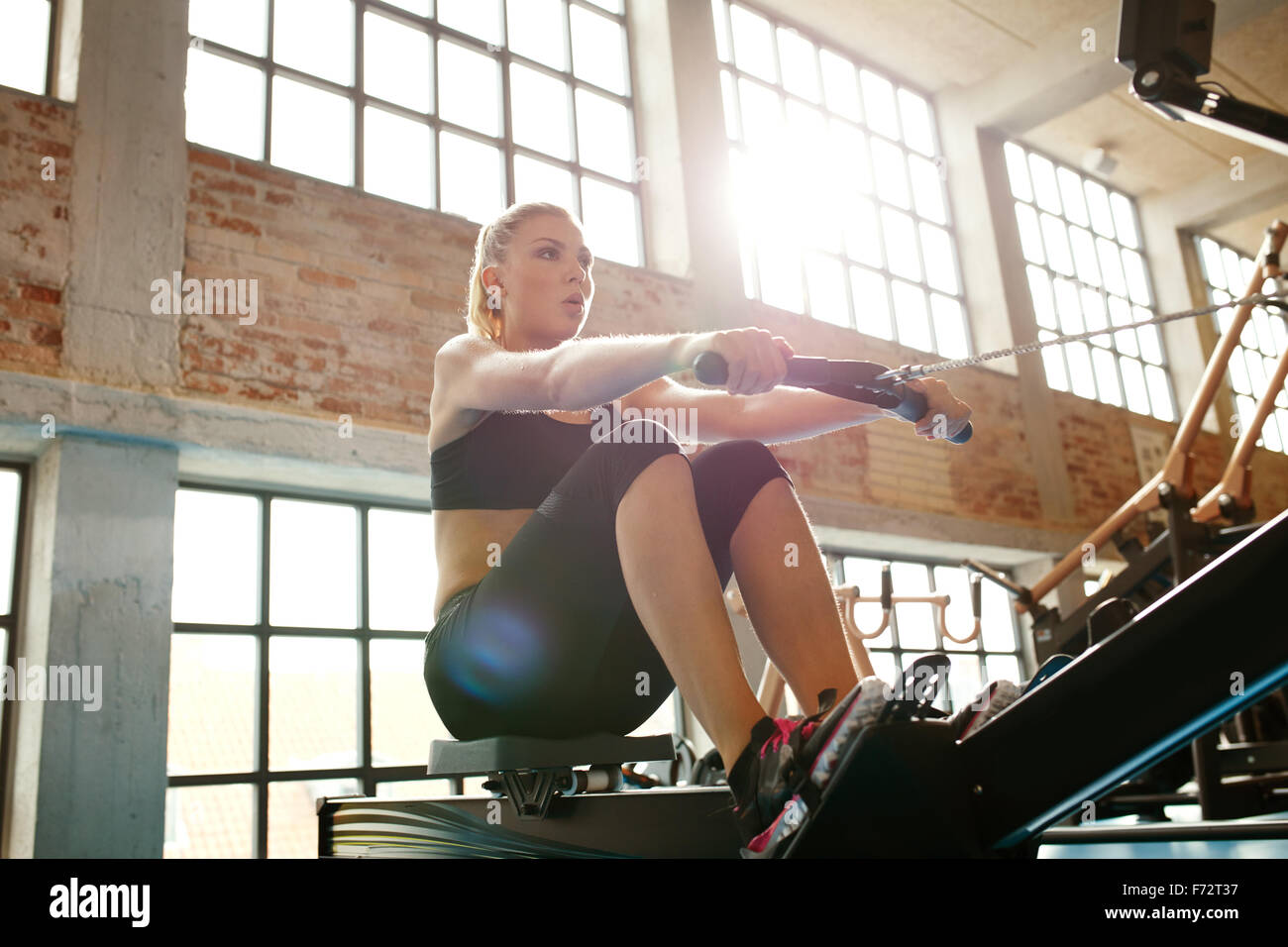 Young caucasian woman doing exercises on fitness machine in gym. Female using rowing machine at  fitness club. - Stock Image