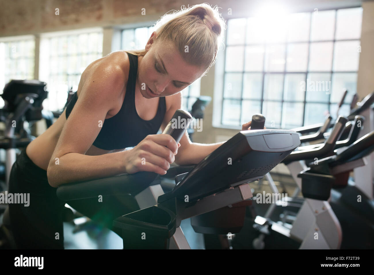 Fitness woman on bicycle doing cardio workout at gym. Fit young female exercising on gym bike. - Stock Image