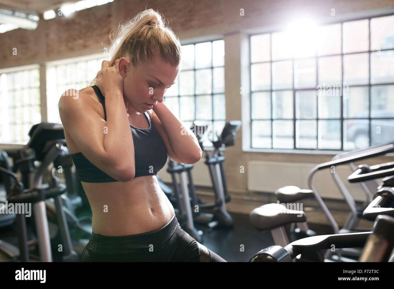 Indoor shot of young woman feeling tired after working out on stationary bikes in gym. Relaxing her neck muscles. Stock Photo