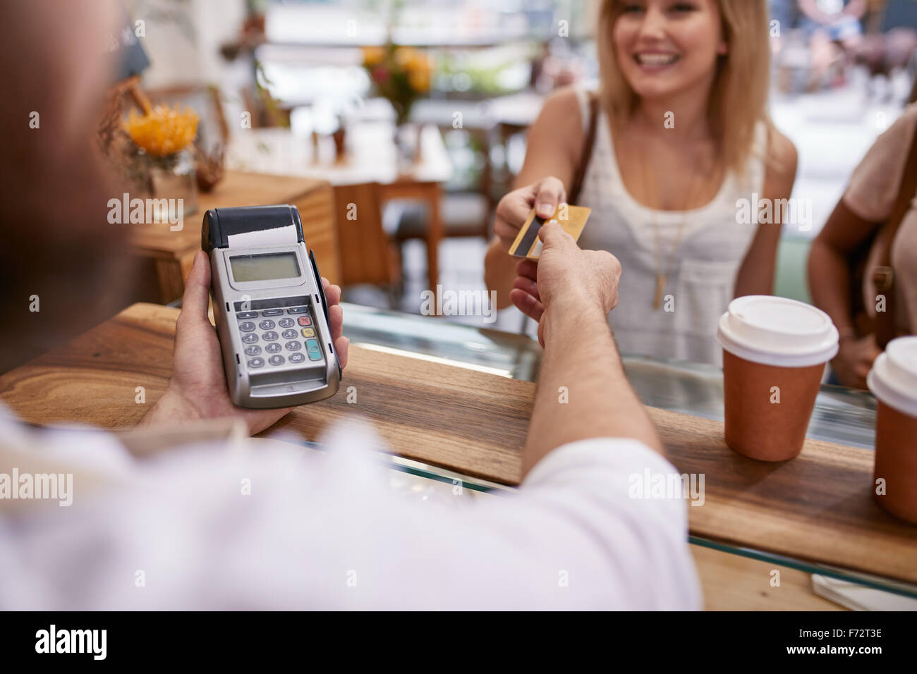 Customer paying for their order with a credit card in a cafe. Bartender holding a credit card reader machine and - Stock Image
