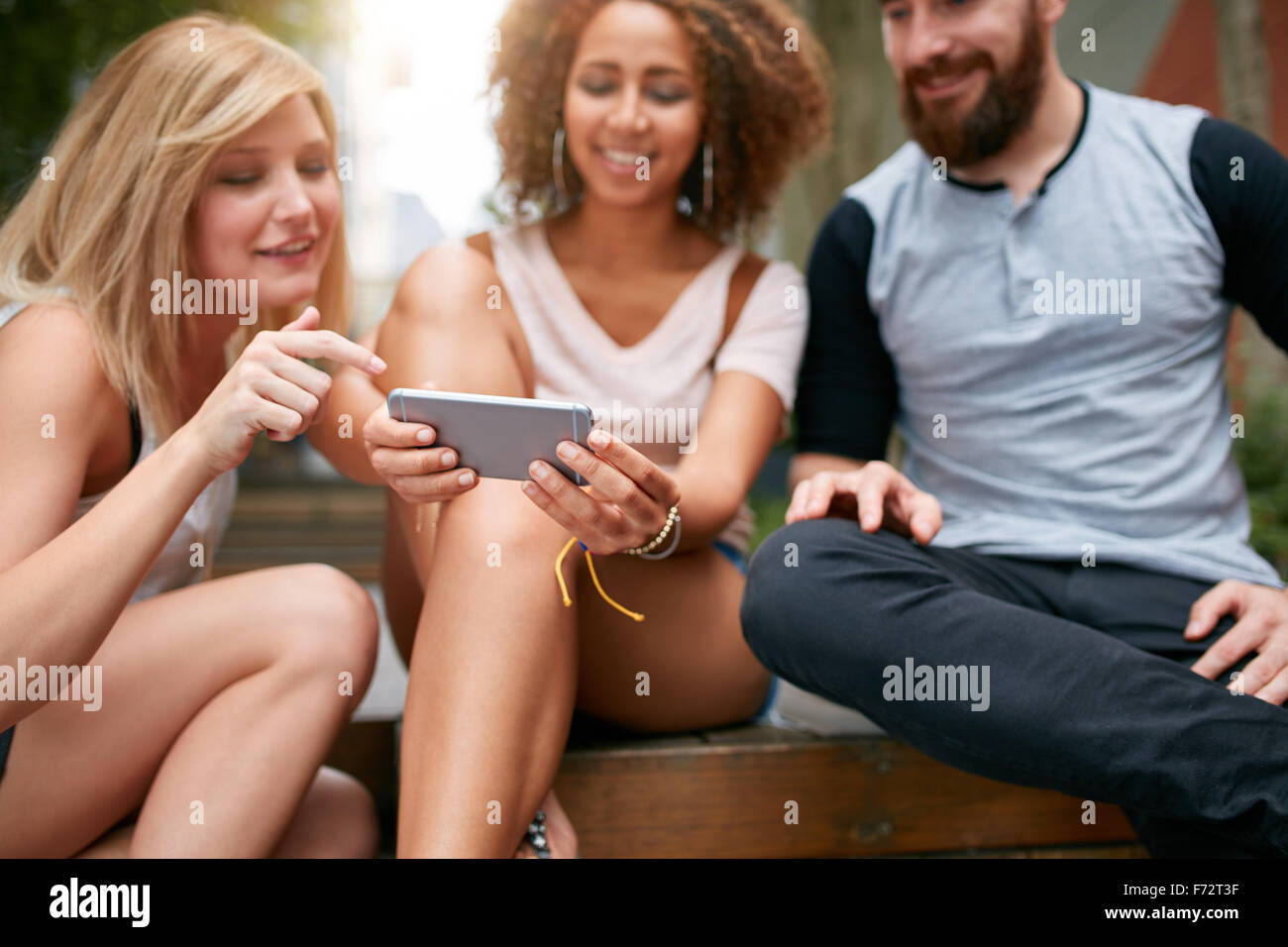 Close up shot of young adults looking something interesting on cellphone. Young friends using mobile phone while - Stock Image