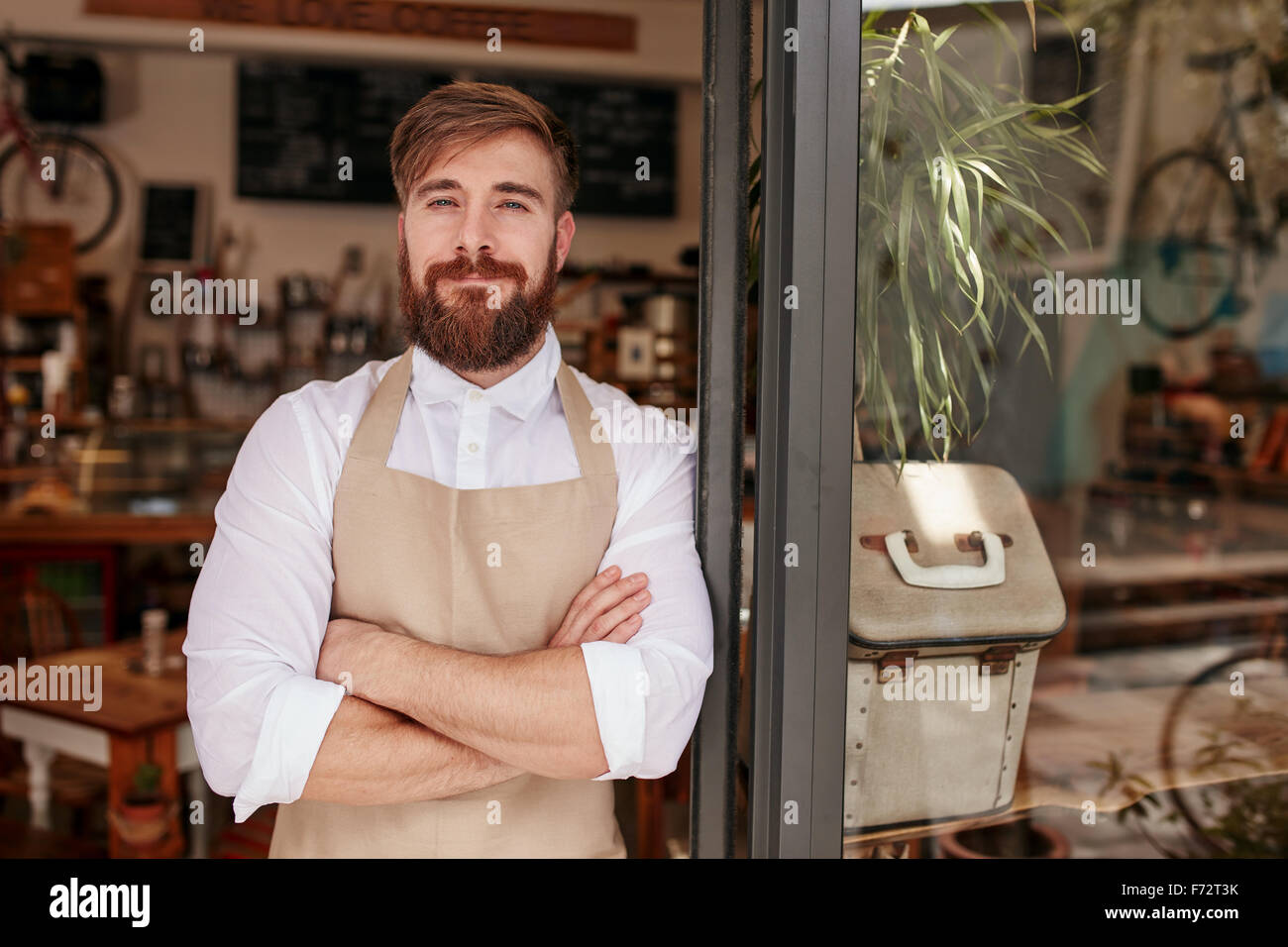 Portrait of a handsome and confident cafe owner standing at the door. Young man standing with his arms crossed looking - Stock Image