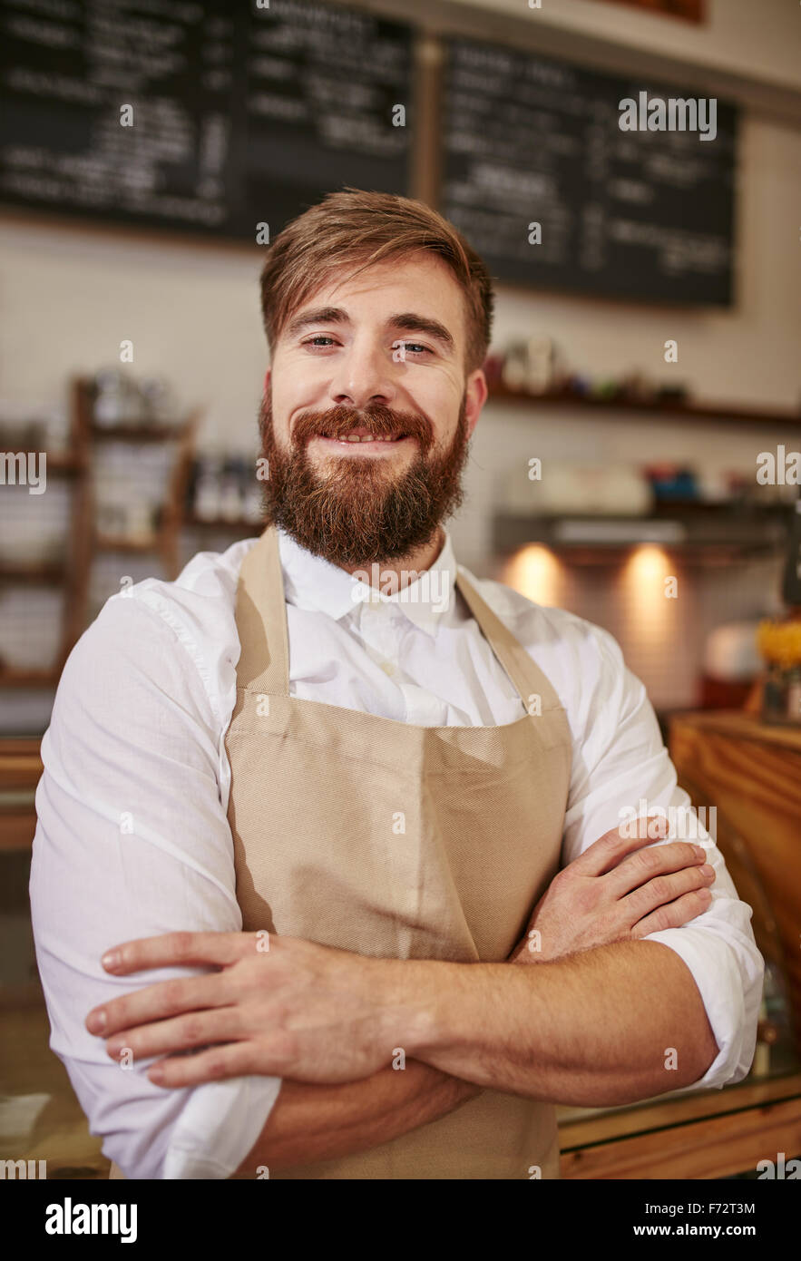 Portrait of happy young barista at work. Caucasian man wearing apron standing with his arms crossed and looking - Stock Image