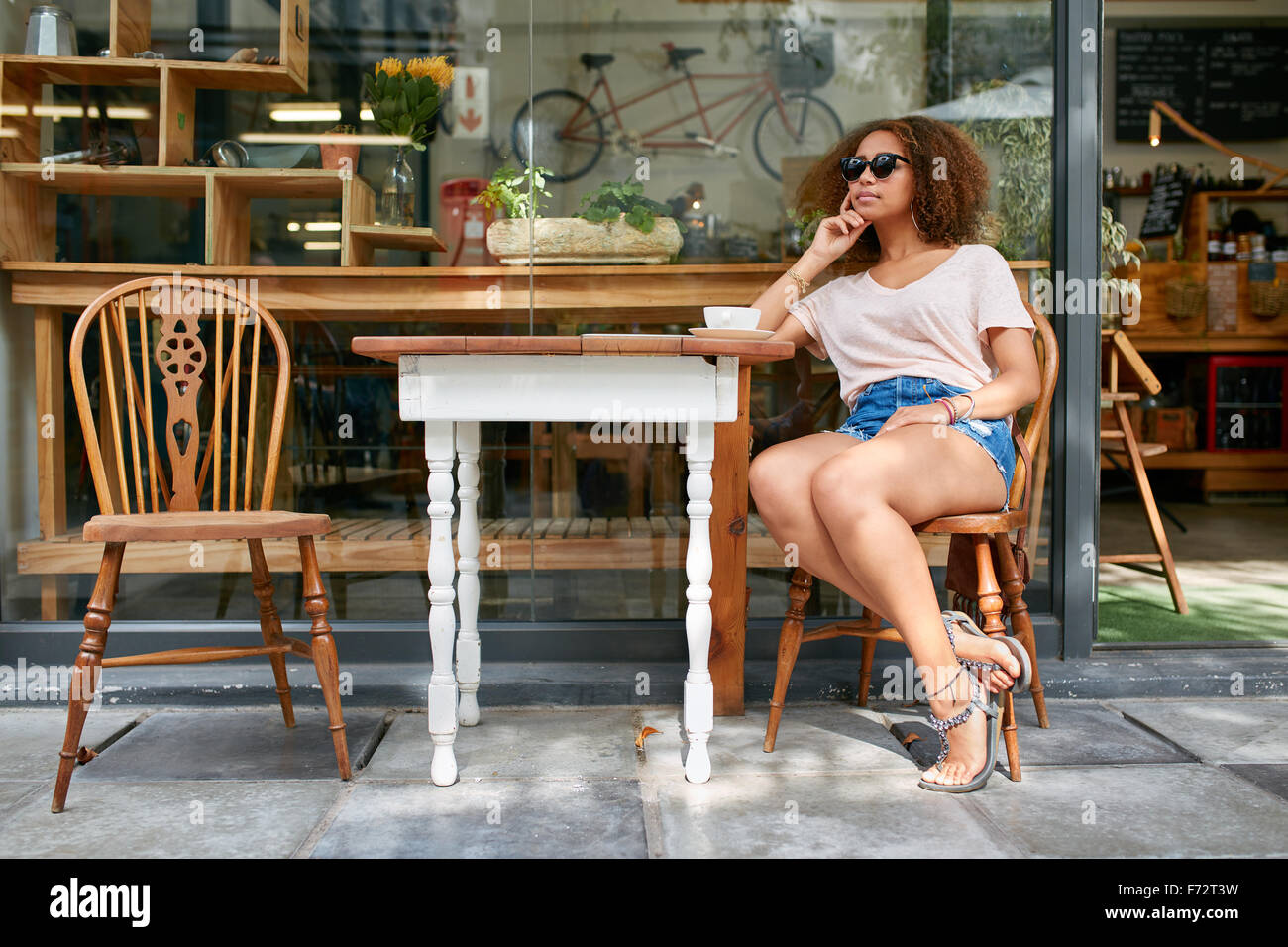 Portrait of stylish young woman sitting alone outdoors at sidewalk cafe looking away and thinking. Young african - Stock Image