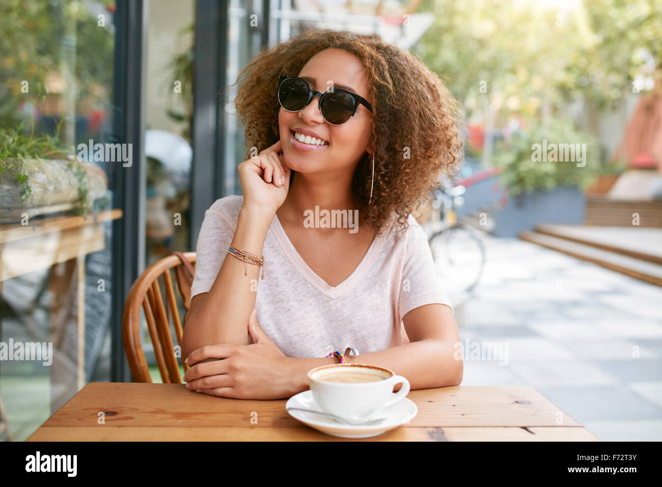 Portrait of cute young girl sitting at outdoor cafe looking at camera and smiling. African young woman at sidewalk - Stock Image