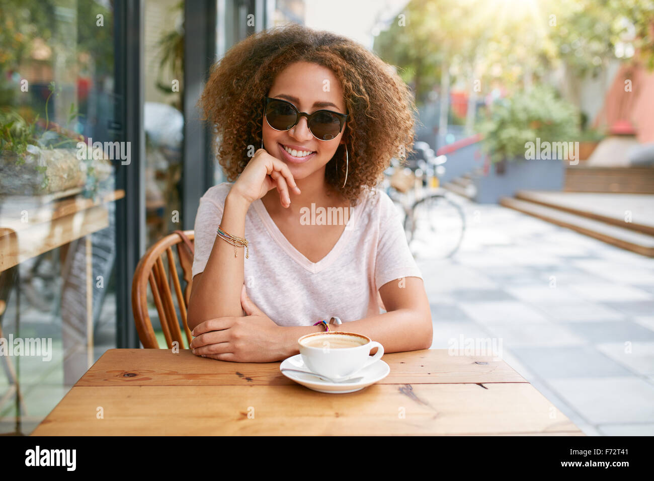 Portrait of attractive young woman sitting at outdoor coffee shop with a cup of coffee. African young stylish girl - Stock Image
