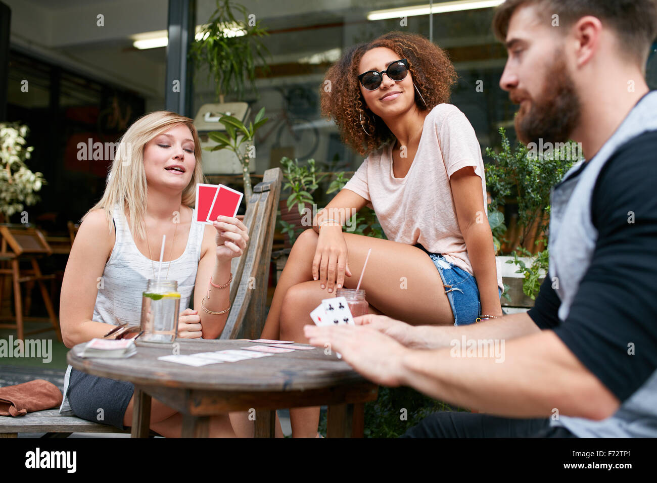 Group of young people sitting at the table and playing cards. Friends playing card game while sitting at outdoor - Stock Image