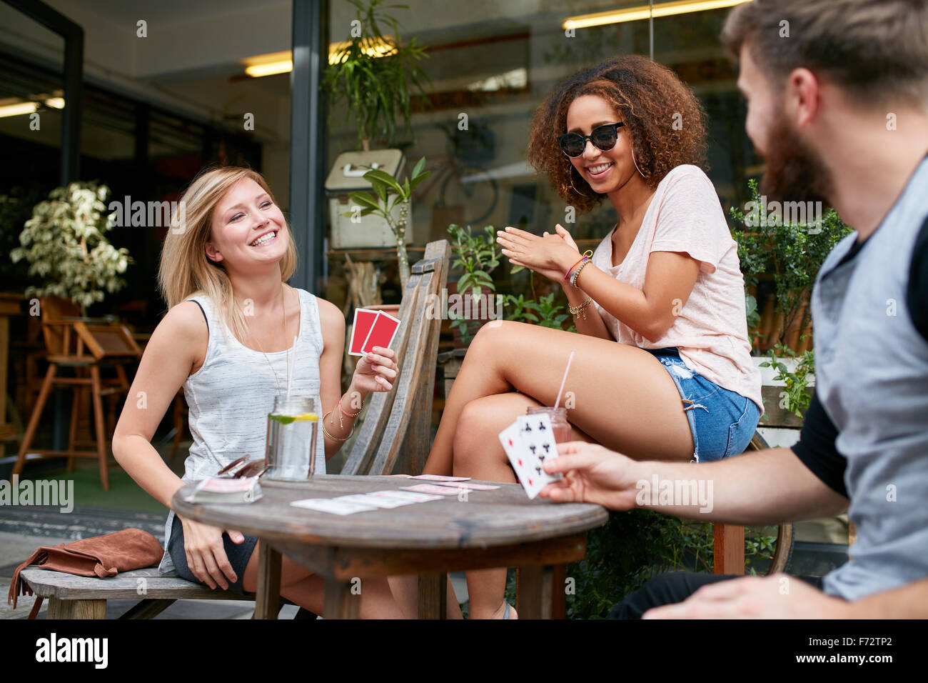 Three friends sitting in outdoor cafe and playing cards and having fun. Happy young people at sidewalk coffee shop - Stock Image