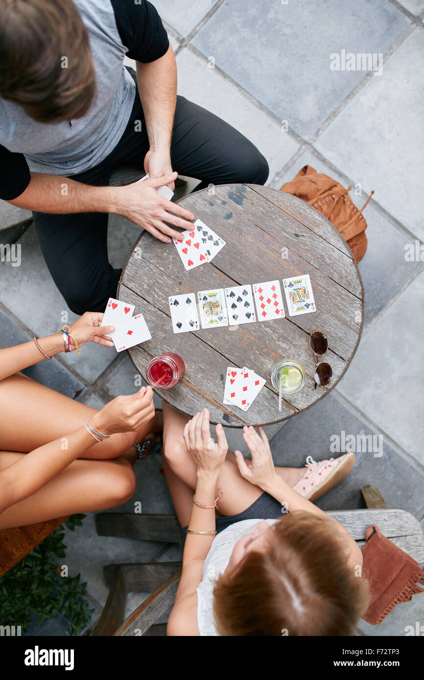 Three young friends playing cards at cafe. Directly above shot of young man and women sitting around an outdoors - Stock Image