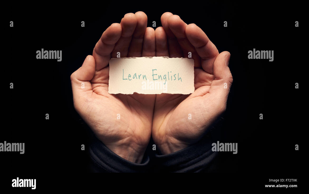 A man holding a card in cupped hands with a hand written message on it, Learn English. - Stock Image