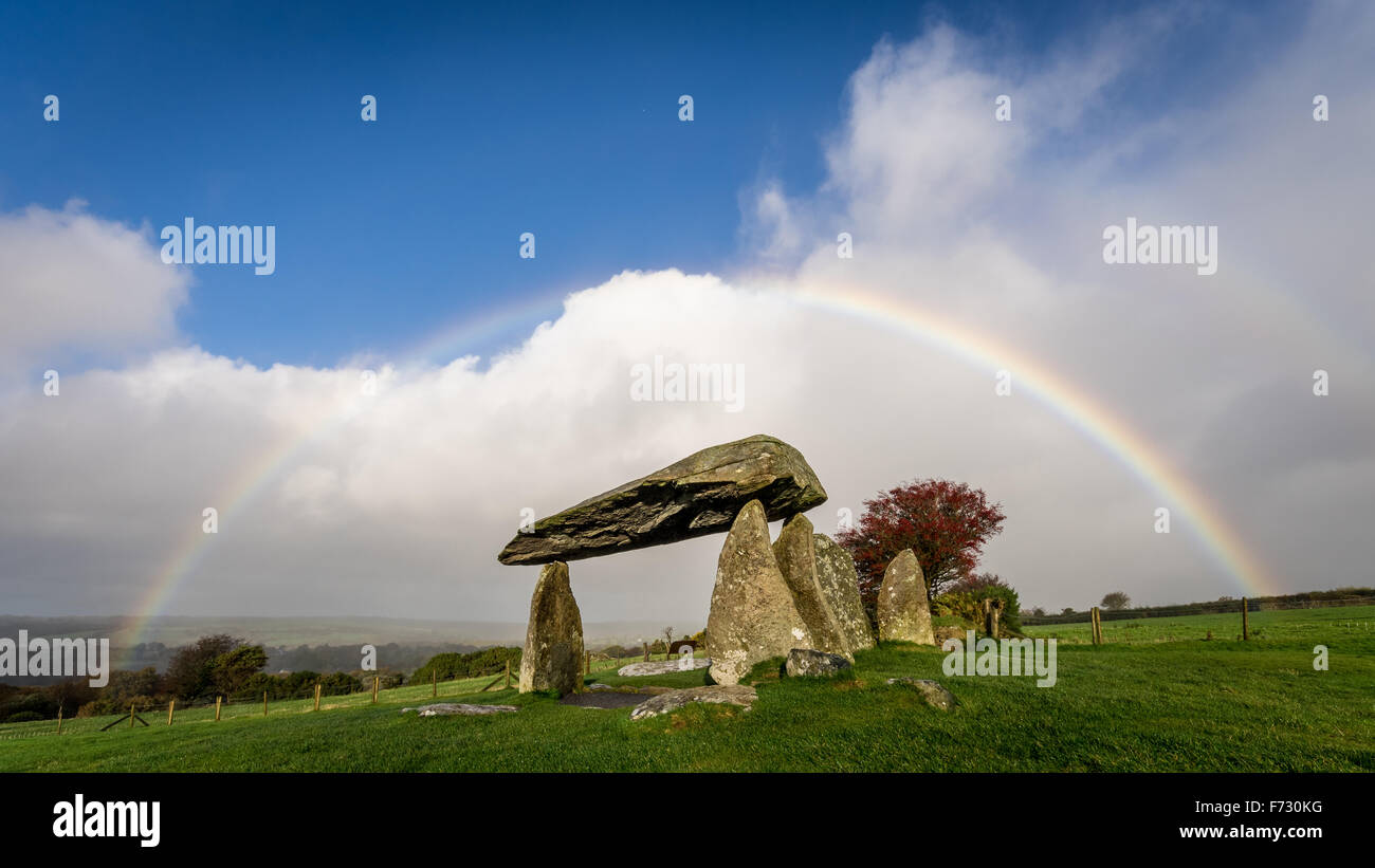 Pentre Ifan, the largest and best preserved neolithic dolmen in Wales, under a rainbow, with blue sky and clouds. - Stock Image