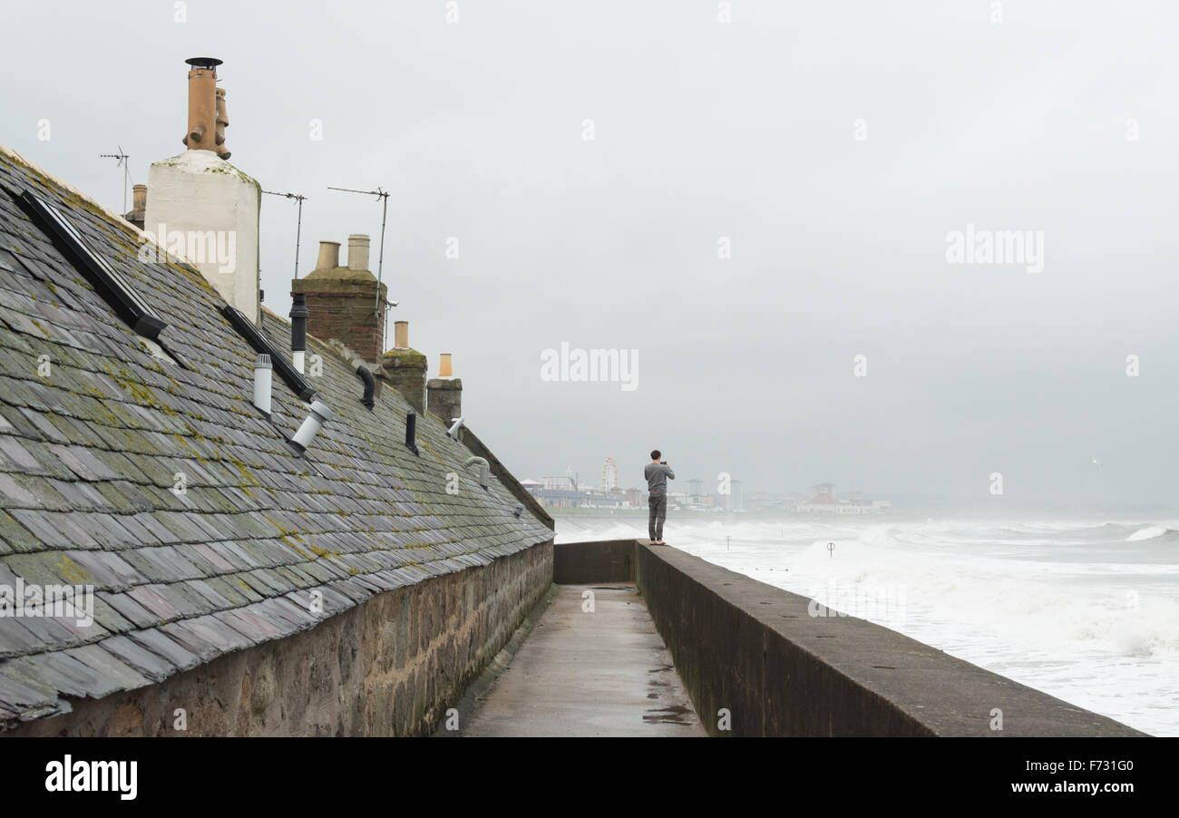 Young man taking photos from the sea defence wall which protects old fisherman's cottages at Footdee, Aberdeen, - Stock Image