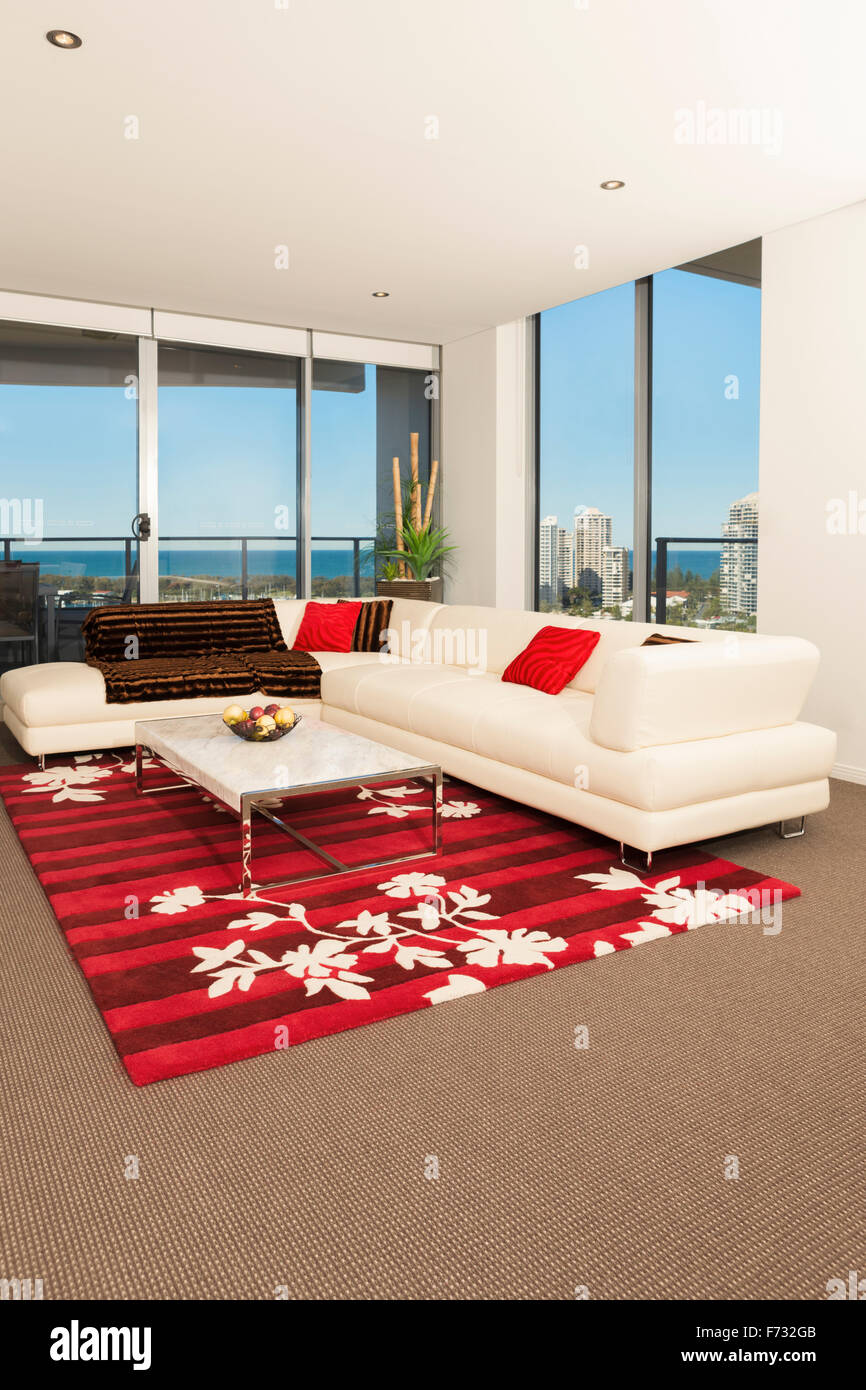 Image Of A Spacious Living Room With A White Sofa, Red Carpet And Big  Windows