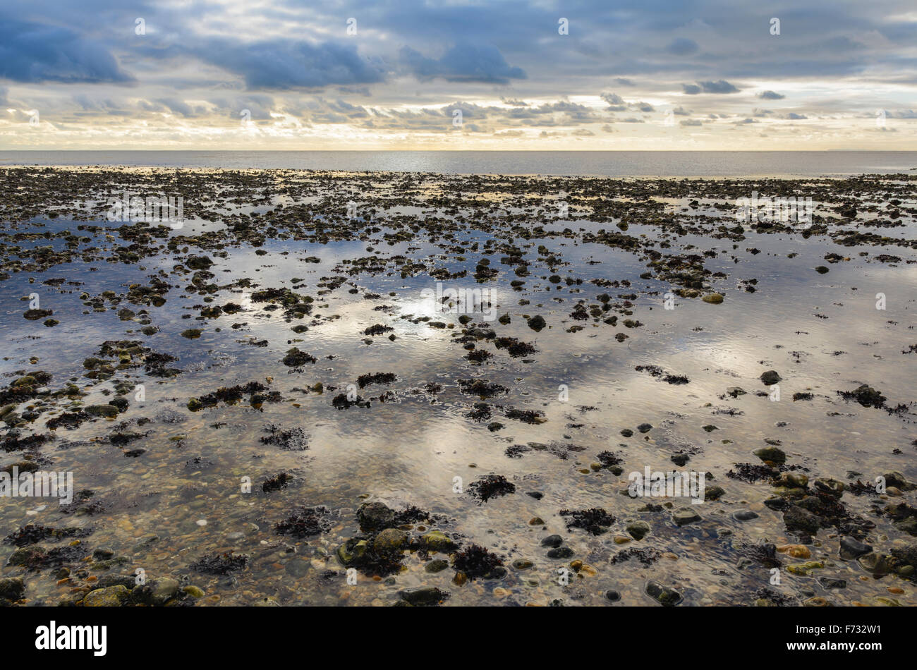 Reflections of the sky in the sea at low tide, on a deserted beach. - Stock Image