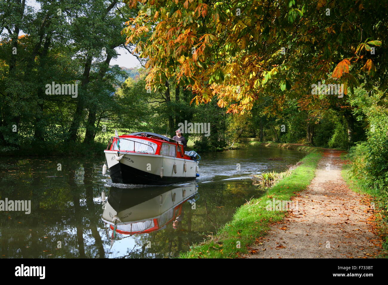 Boating on the the calm water of the Monmouthshire and Brecon Canal in Autumn. - Stock Image
