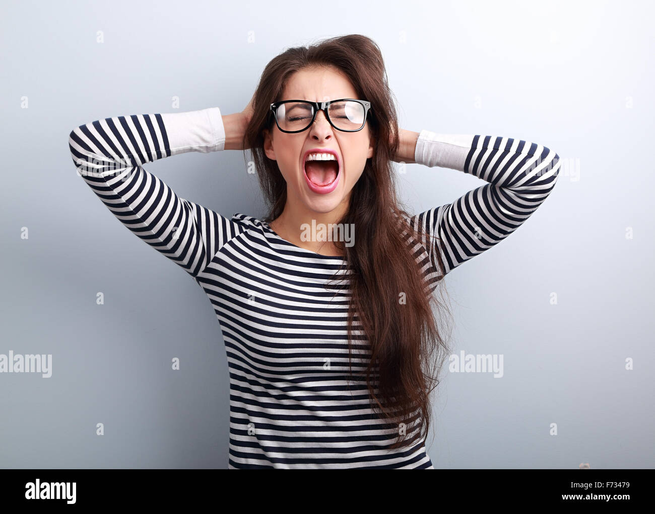 Anger young business woman in glasses strong screaming with wild open mouth and holding head the hands on blue background - Stock Image