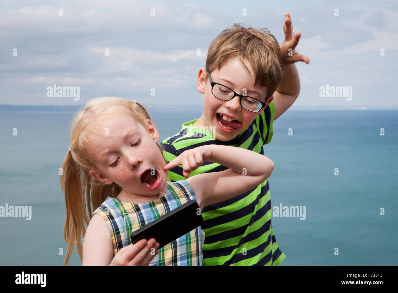 Brother and sister making faces and taking a selfie with a smart phone. - Stock Image