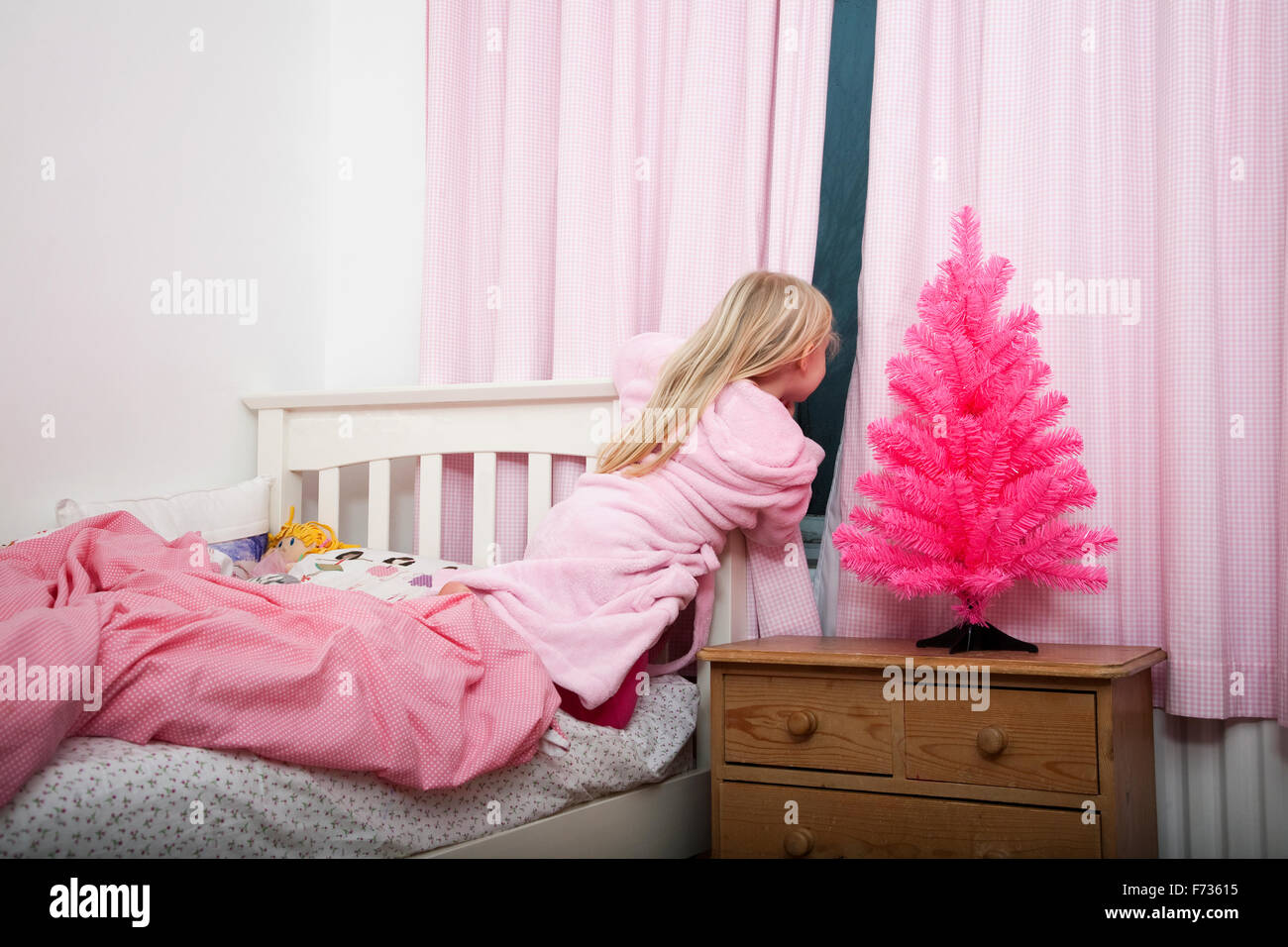 A girl peering through the curtains in her bedroom into the night at Christmas. - Stock Image