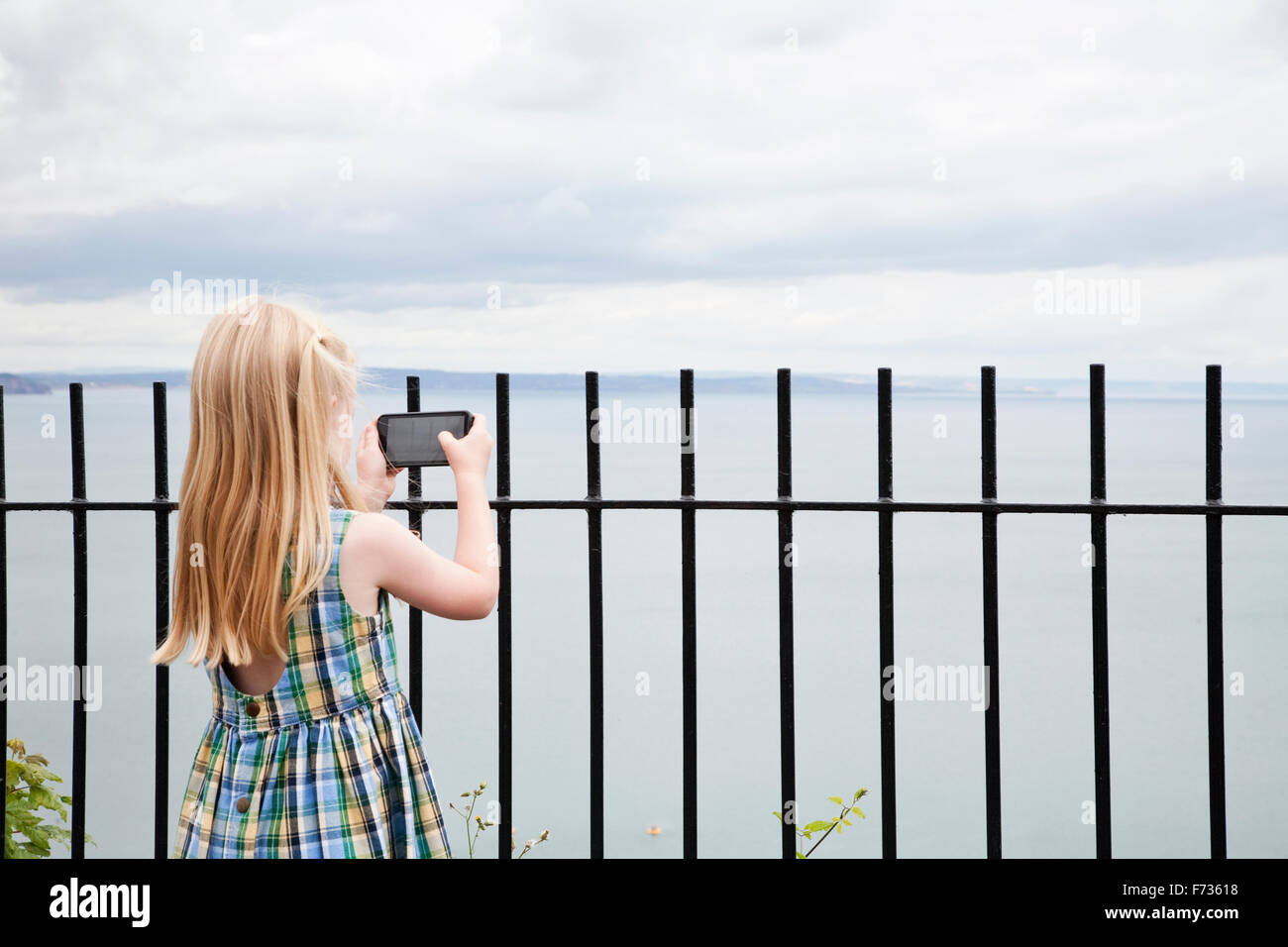 A girl in a checked sundress taking a photograph with a smart phone. - Stock Image