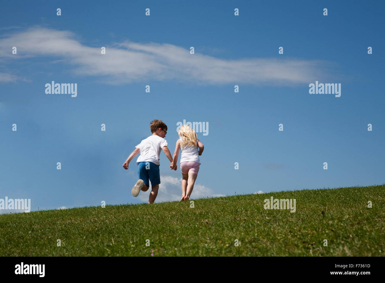 Two children running up a hill - Stock Image
