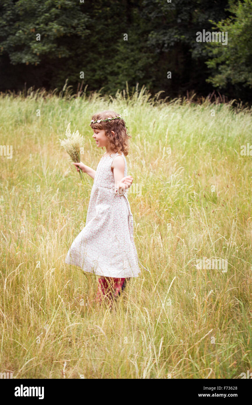 Young girl with flowers in her hair picking wild flowers in a meadow. - Stock Image