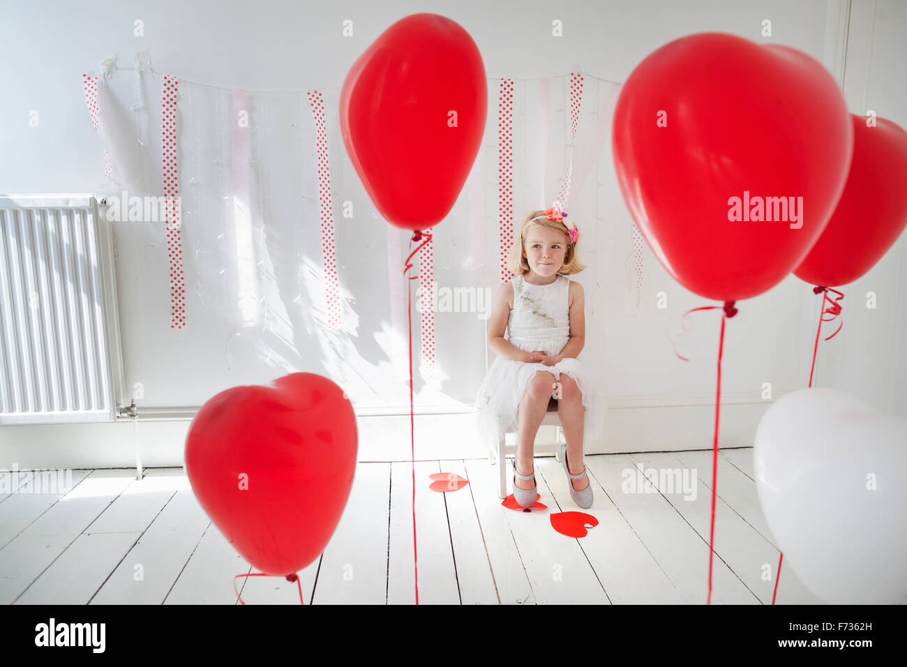 Young girl posing for a picture in a photographers studio, surrounded by red balloons. - Stock Image