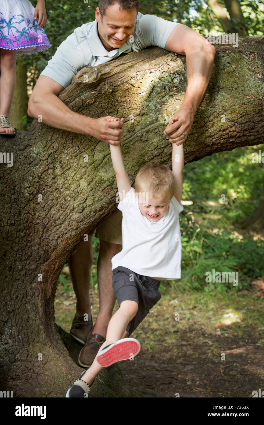Father playing with his son by a tree in a forest. - Stock Image