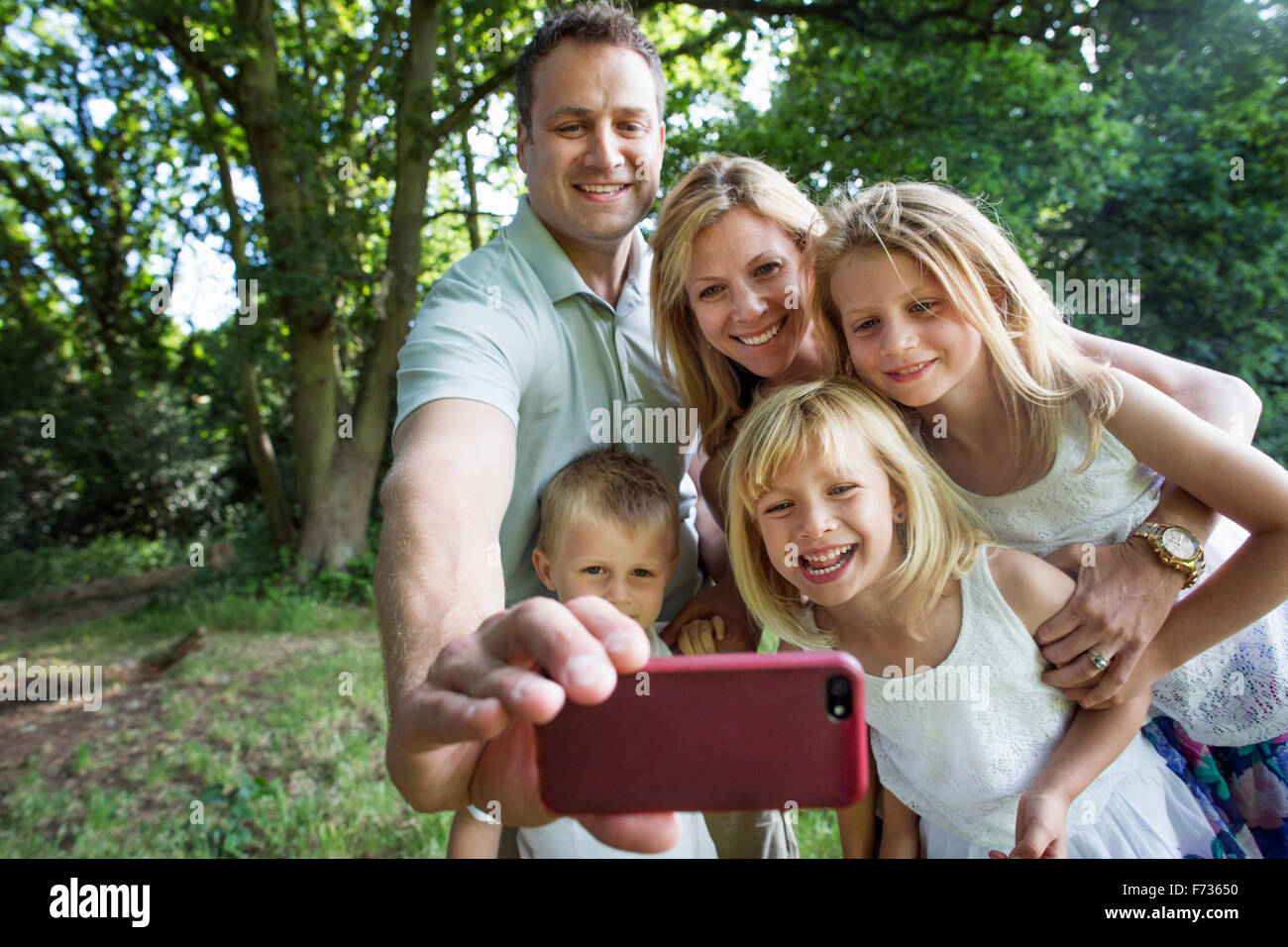 Family with three children, taking a selfie. - Stock Image