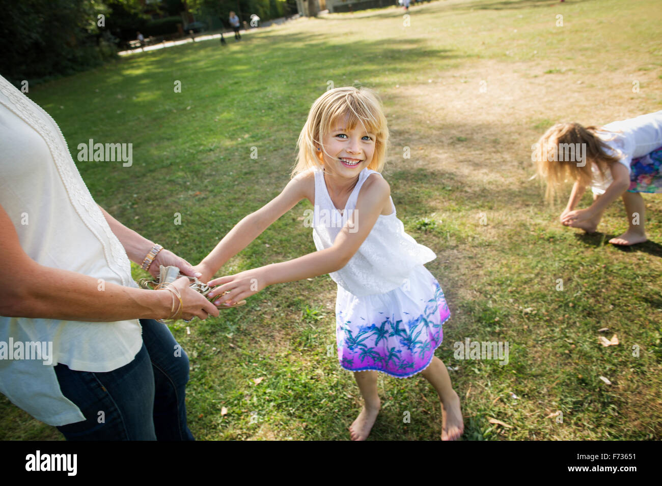 Mother playing with her daughters in a park. - Stock Image