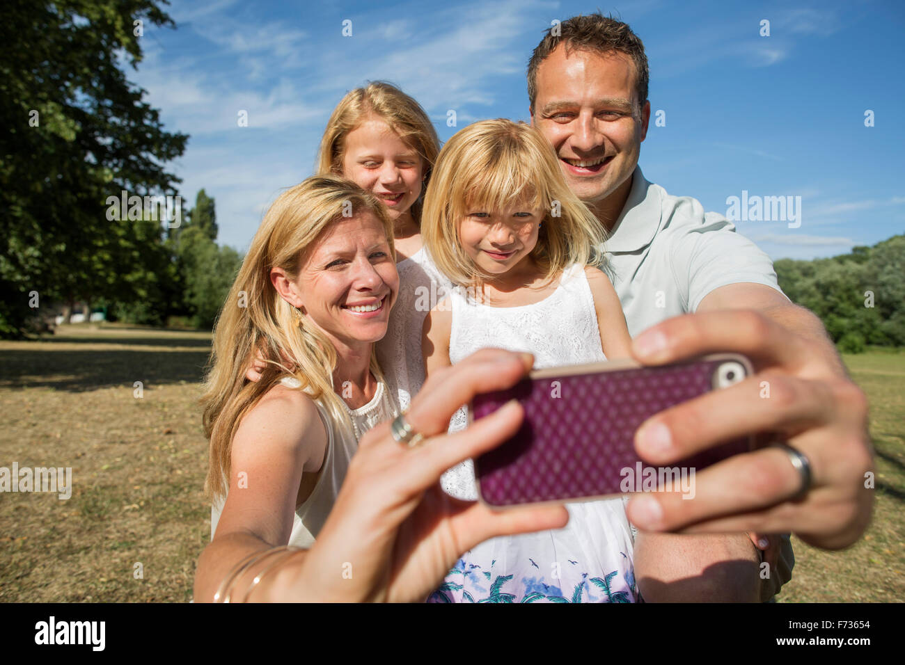 Family with two children, taking a selfie. - Stock Image