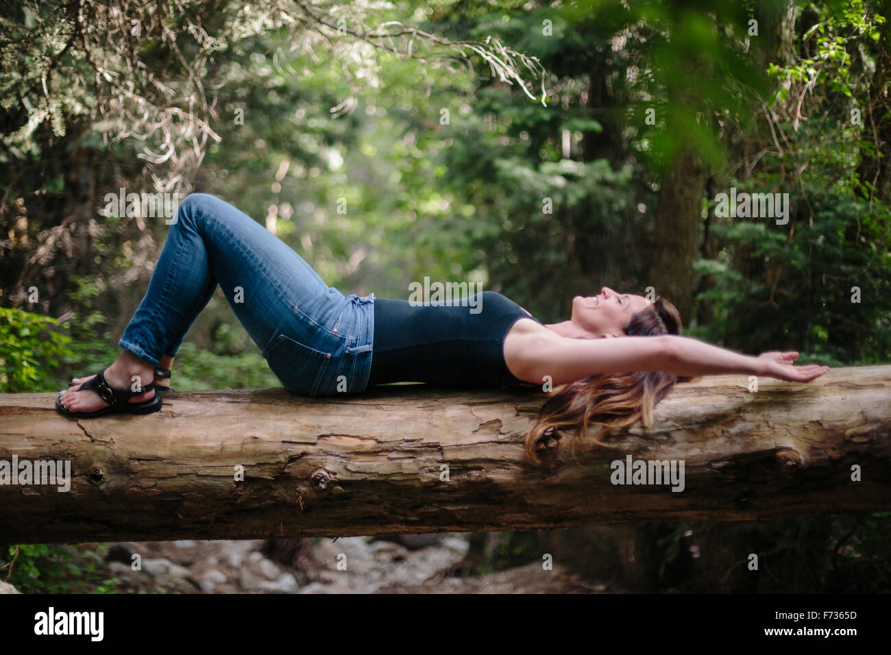 Woman lying on her back on a fallen tree trunk in a forest. - Stock Image