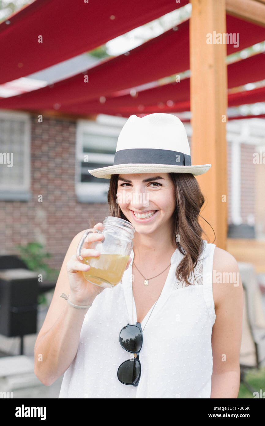 Smiling woman standing in a garden, holding a drink. - Stock Image