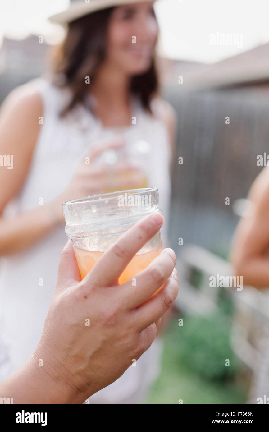 Close up of a hand holding a drink, a woman in the background. - Stock Image