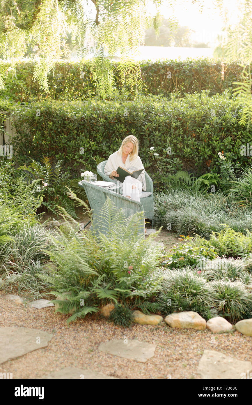 Blond woman sitting in a wicker chair in a garden, reading. - Stock Image