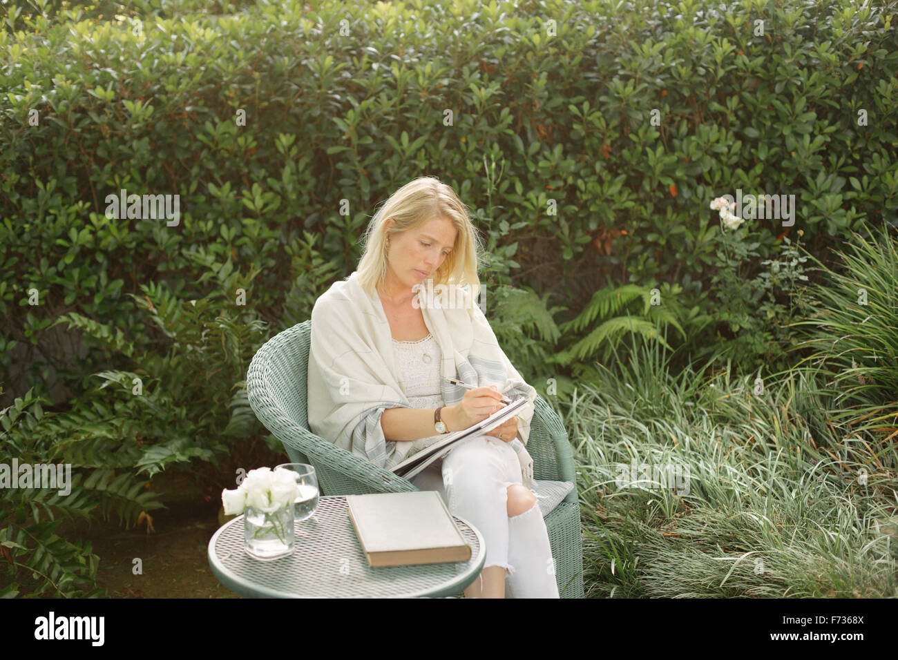 Blond woman sitting in a wicker chair in a garden, writing. - Stock Image