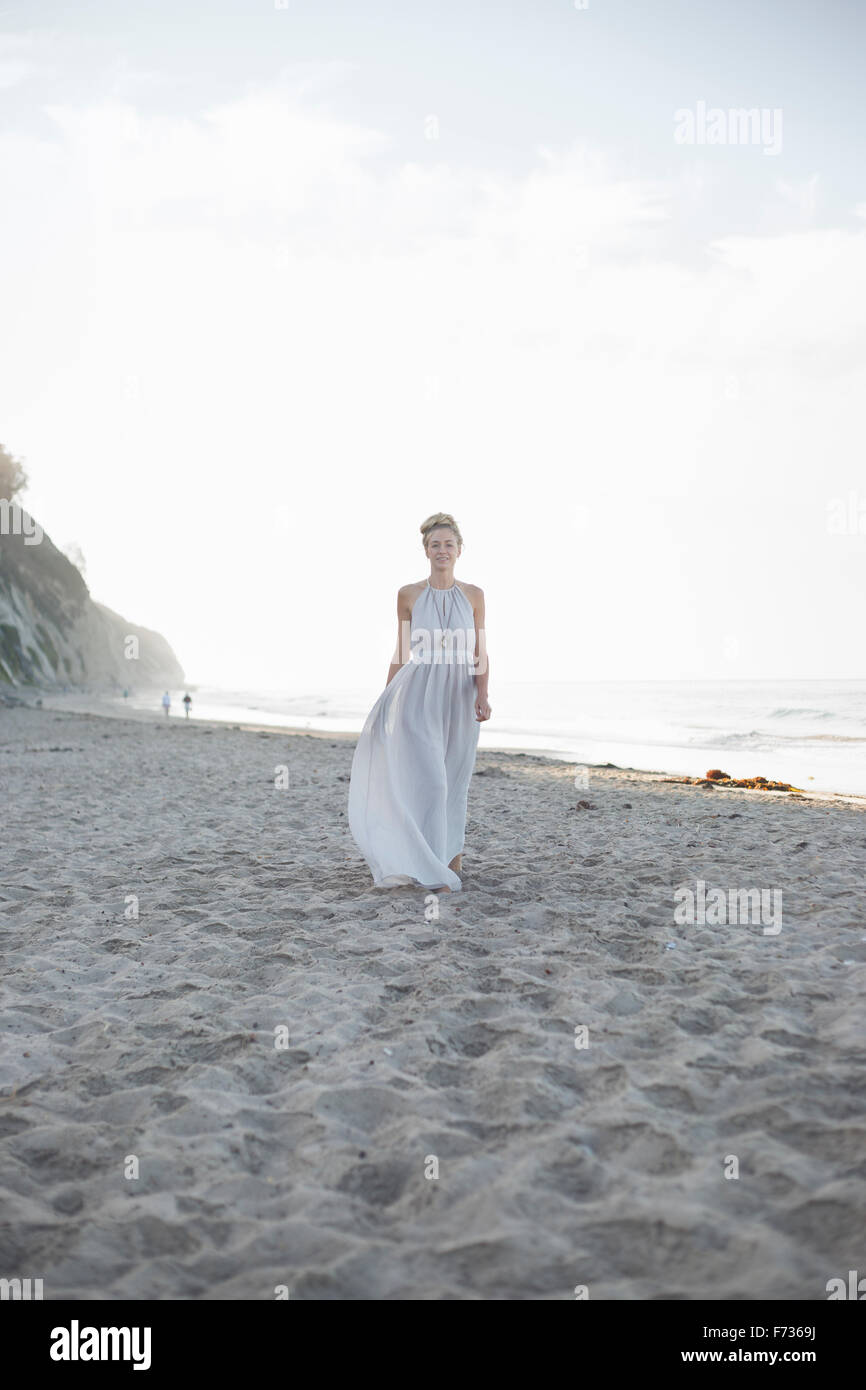 Blond woman wearing a long dress standing on a sandy beach. - Stock Image