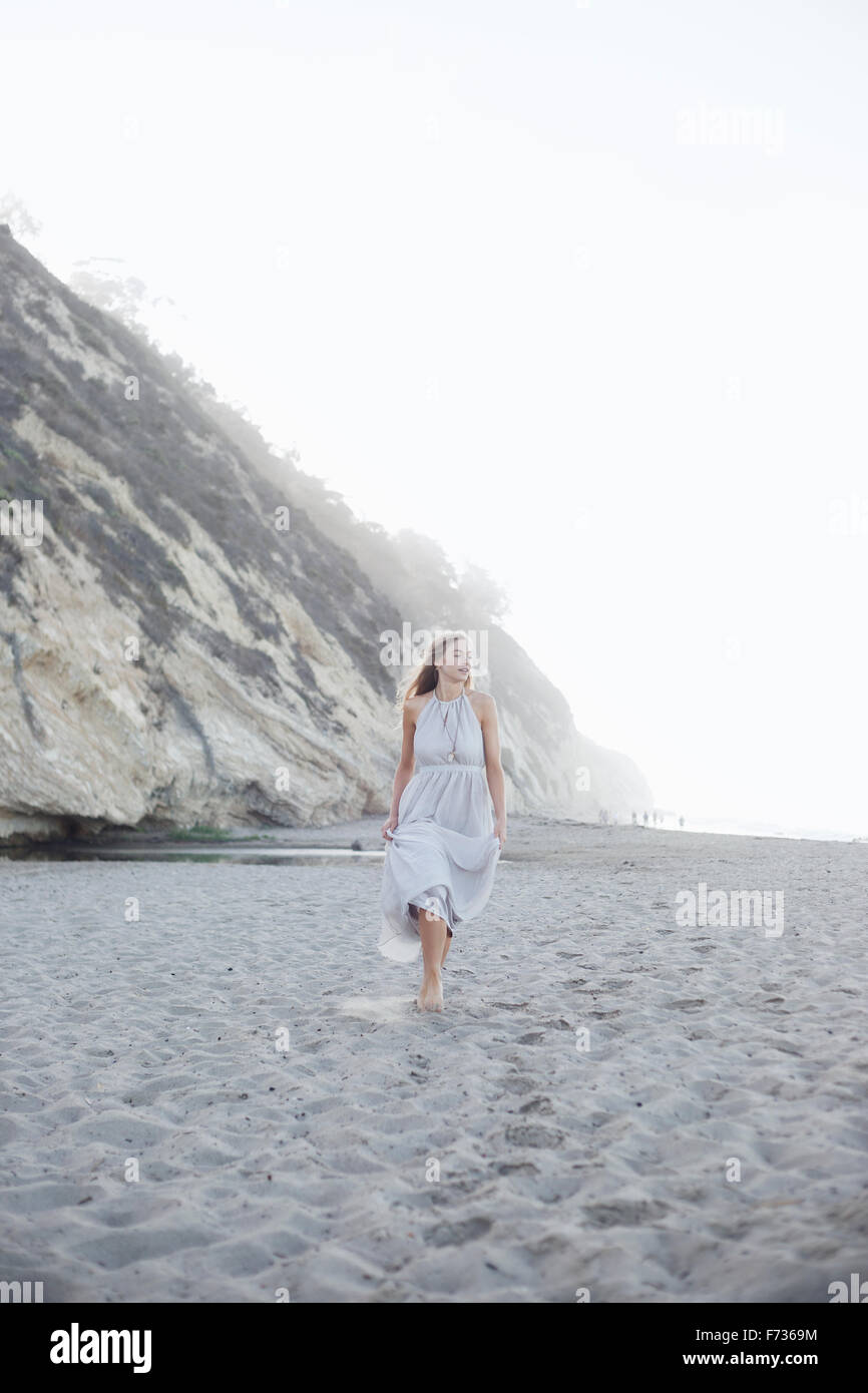 Blond woman walking on a sandy beach near a cliff. - Stock Image