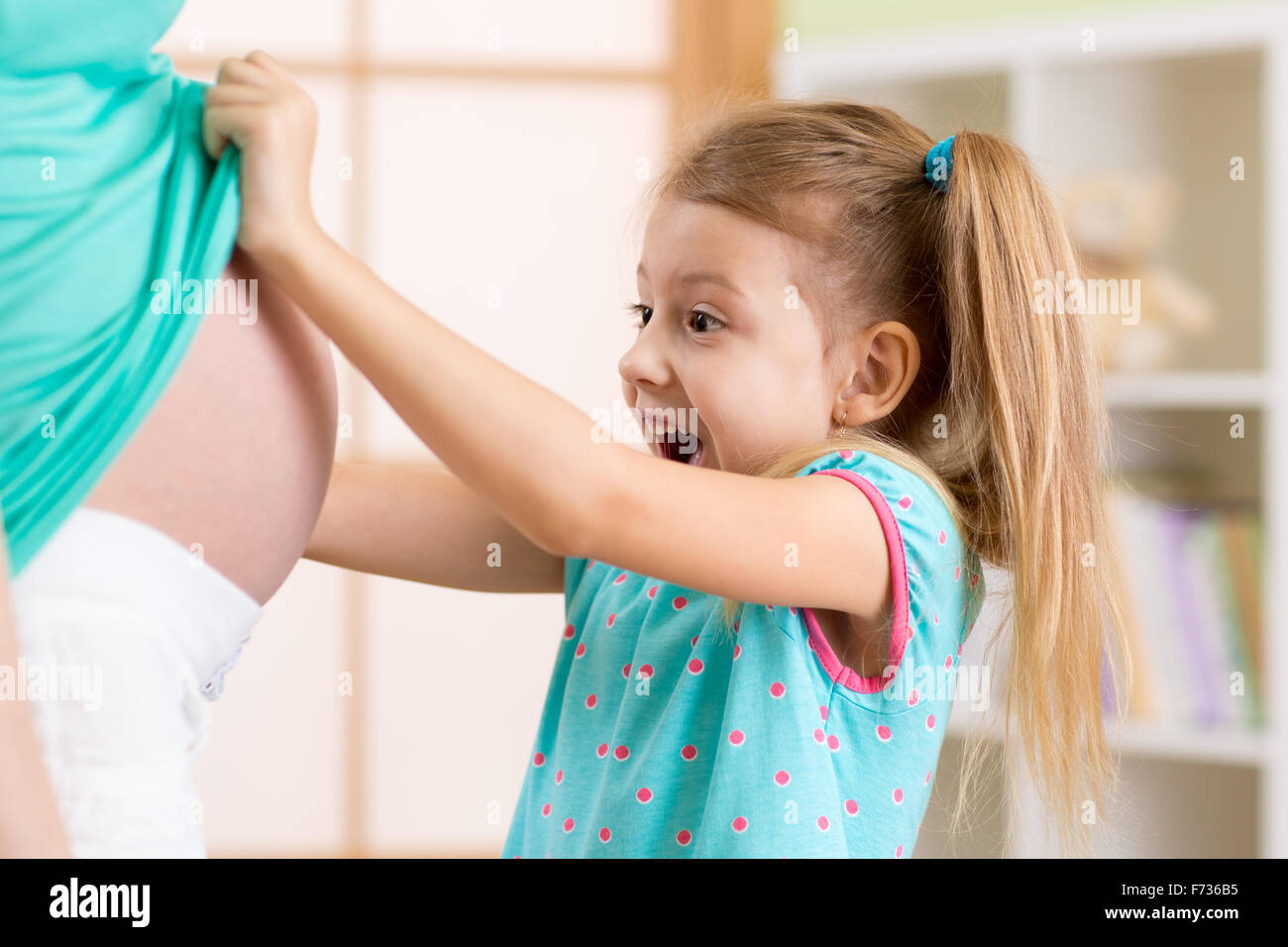 Little child girl looking at mother pregnant tummy - Stock Image