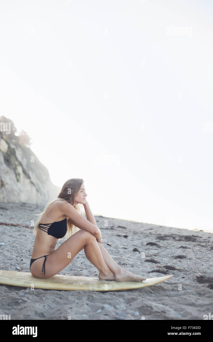 Blond woman in a black bikini sitting on a surfboard on a sandy beach. - Stock Image