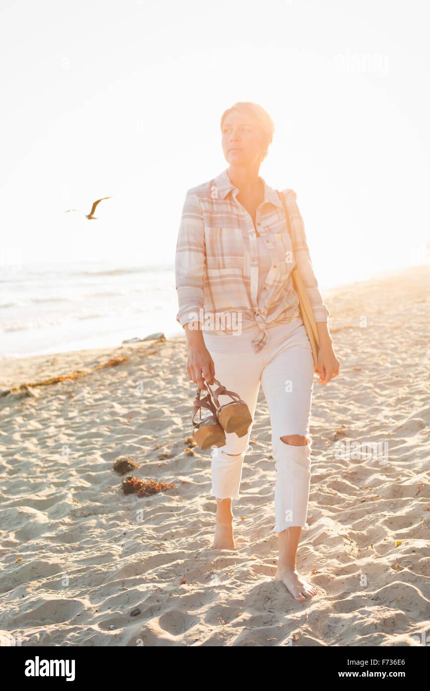 Woman walking along a sandy beach by the ocean. - Stock Image
