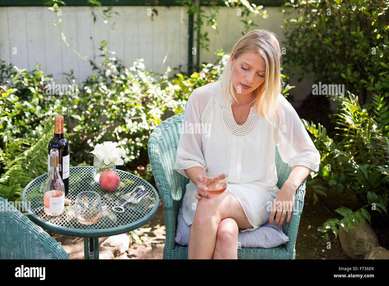 Blond woman sitting in a garden in summer, holding a wine glass. - Stock Image