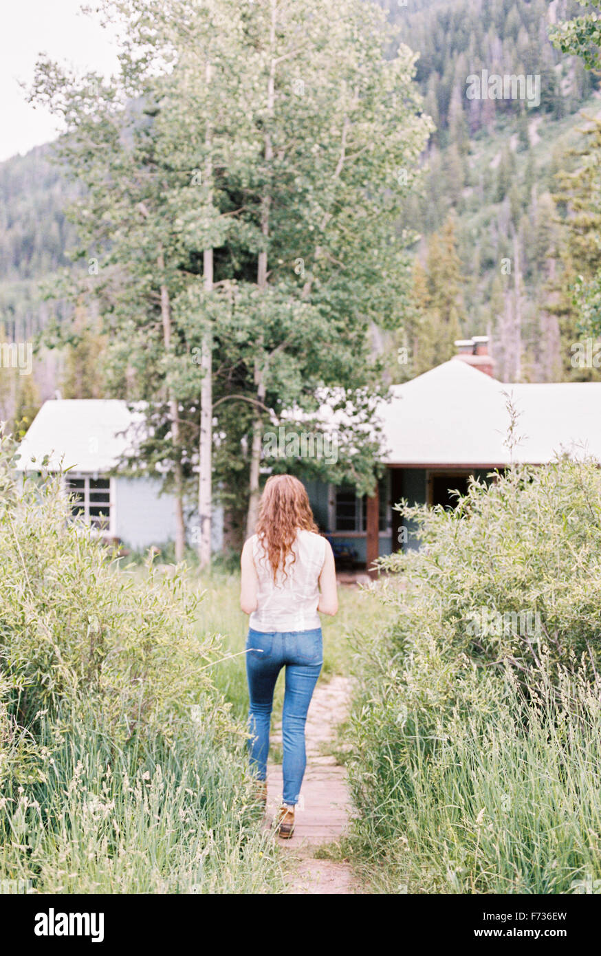 Woman walking along a footpath on a ranch. - Stock Image