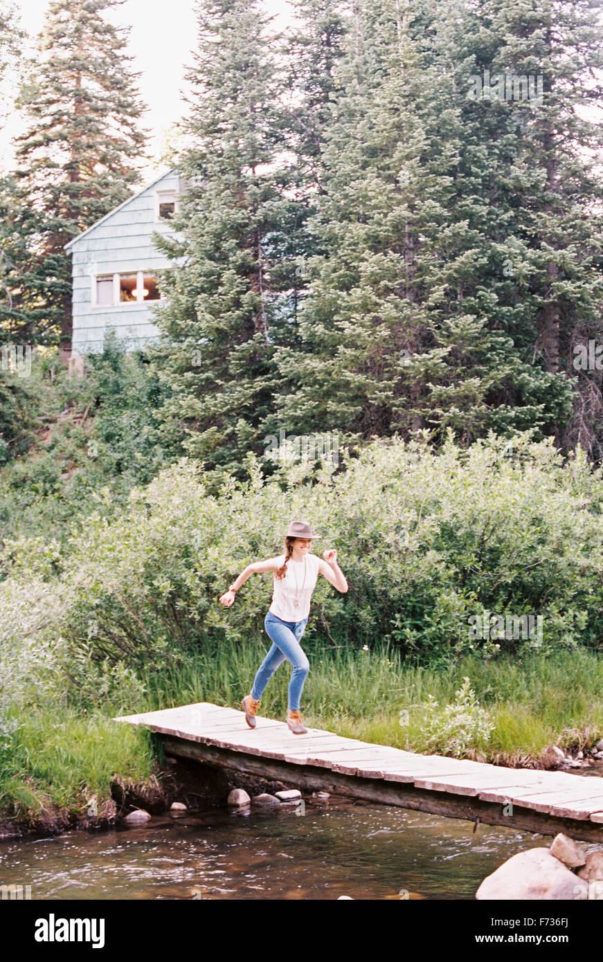 Woman running across a wooden bridge over a stream. - Stock Image